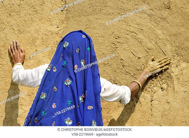 India, Rajasthan, Tonk region, Woman refurbishing her home walls with a coat of fresh clay prior to Diwali festival
