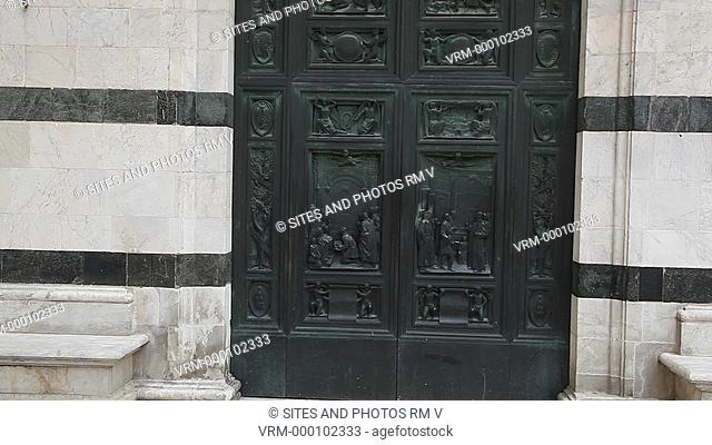 Exterior, HA, TILT up, daylight, view of the Bronze door Porta del Perdono, at the base of the bell tower. Seen above the door lintel is a copy of the marble...