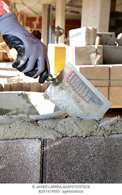 Construction worker using mortar with a trowel, Building hand tool, Donostia, San Sebastian, Gipuzkoa, Basque Country, Spain