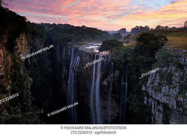 Colorful sunrise skies over a deep waterfall gorge. Magwa Falls, Pondoland, Eastern Cape, South Africa