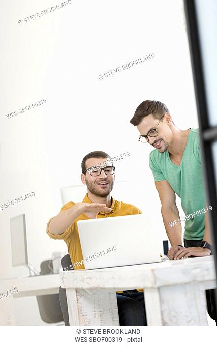 Two businessmen working together in office, using laptop