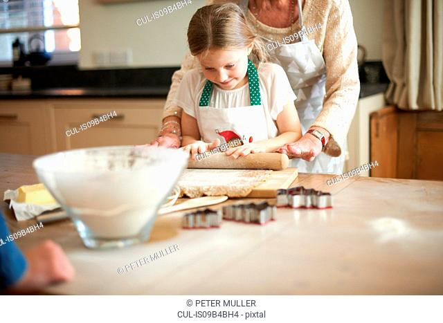 Senior woman and granddaughter rolling dough for Christmas tree cookies