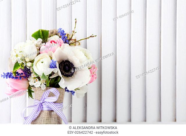 Pastel bouquet from pink tulips, violet grape hyacinths, white anemones, violet veronica and white buttercup with violet ribbon with white wooden shutter...