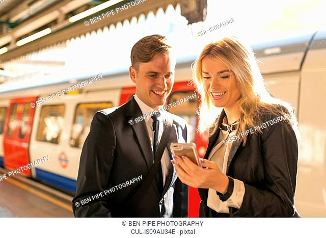 Businessman and businesswoman texting on platform, Underground station, London, UK