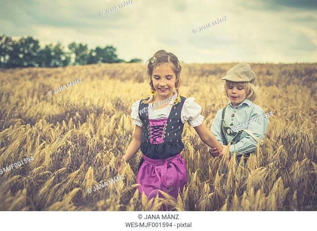 Germany, Saxony, boy and girl walking in a grain field