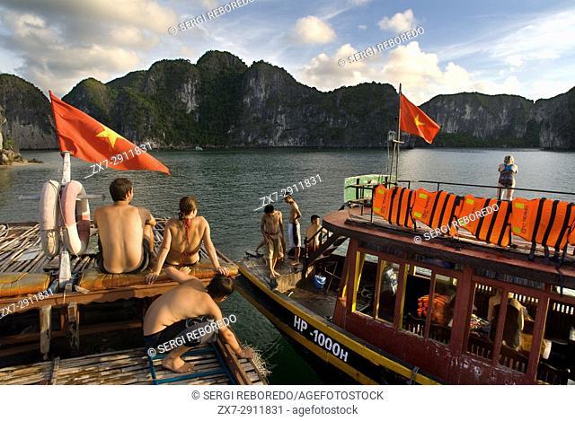 Romatic couple inside a Chinese Junk, Halong Bay Tourist Boat Tour, Vietnam. Junk, boat sailing amongst karst limestone mountains at Cat Ba National Park
