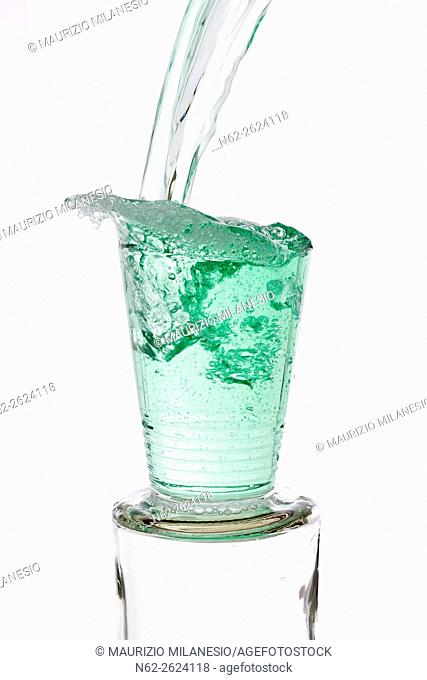 Green drinks poured vigorously overflowing splashing from a glass, on a white background