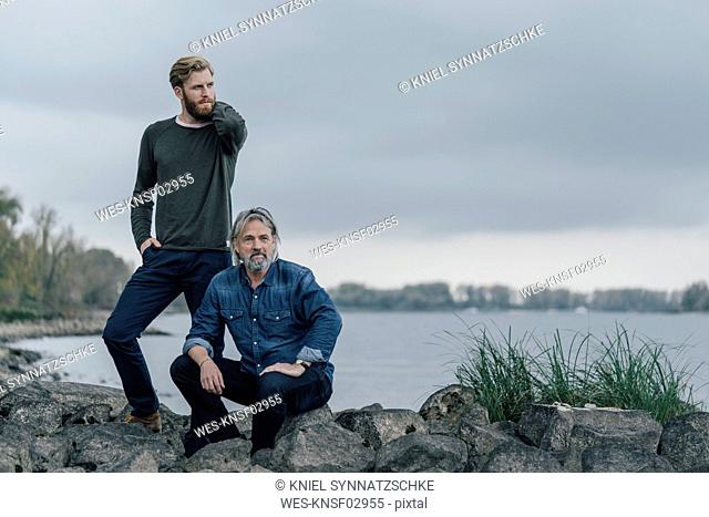 Father and son spending time together outdoors, taking a break, sitting on stones