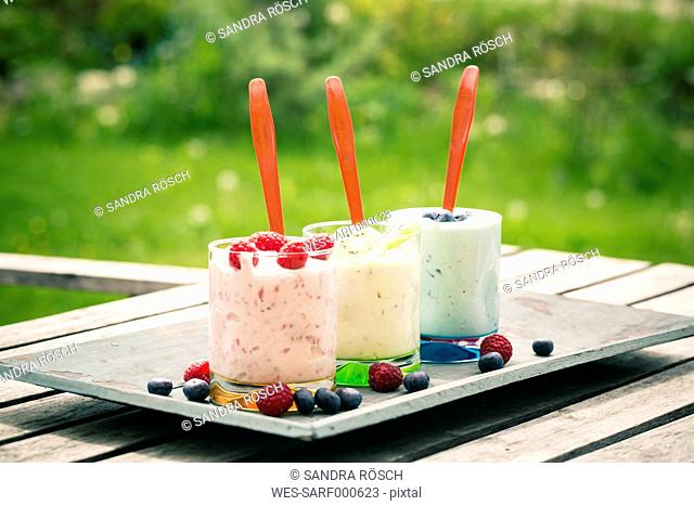 Three garnished glasses of fruit curd on wooden tray