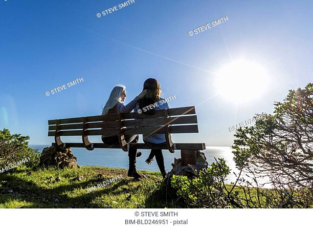Caucasian mother and daughter sitting on bench near ocean