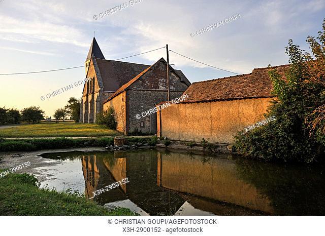 church and farm of the village of Saint-Laurent-la Gatine reflecting on the common pond, Eure-et-Loir department, Centre-Val de Loire region, France, Europe