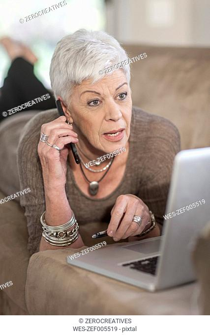 Senior woman with laptop lying on the couch talking on a phone