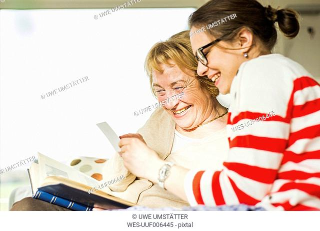 Happy senior woman and young woman sitting on couch looking at photo album
