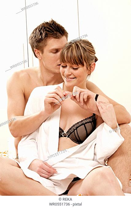 Young couple sitting with condom in bed