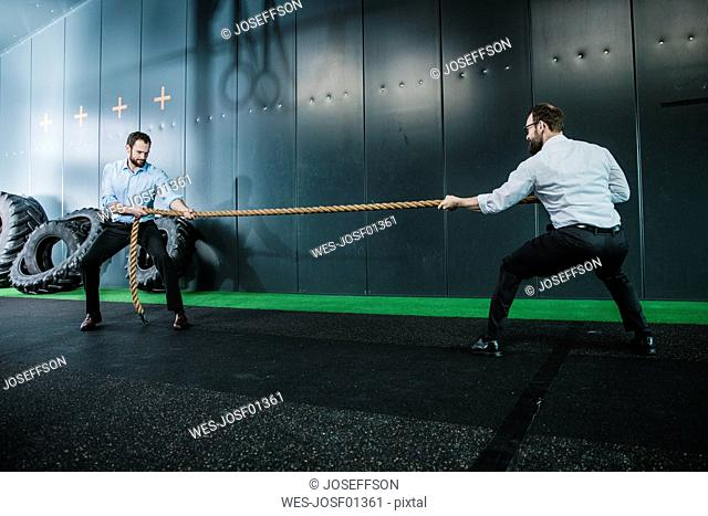 Two businessmen in gym doing tug of war