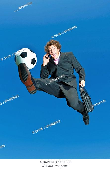 A businessman on a cell phone kicks ball
