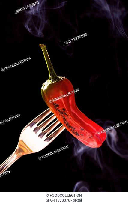 A smoking grilled red chilli pepper on a fork