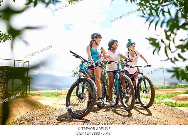 Women friends mountain biking on sunny obstacle course trail