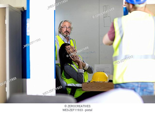 Construction worker and engineer discussing project in site office
