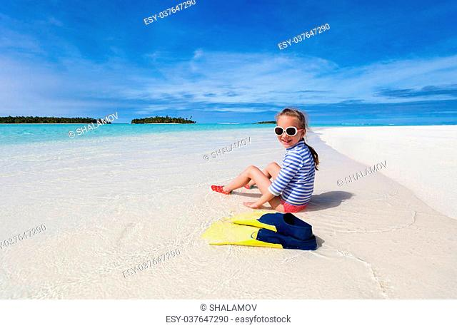 Adorable little girl with snorkeling equipment at beach during summer vacation