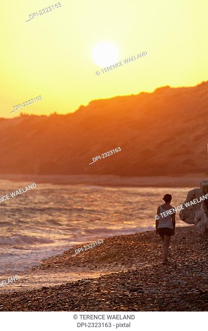 A woman walks along the rock beach at the water's edge at sunset;Aphrodite beach cyprus