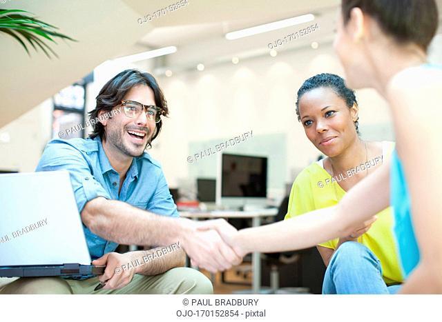 Businessman and businesswoman handshaking in meeting