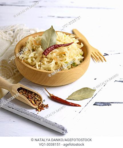 sauerkraut with carrots and green onions in a brown wooden bowl on a white board