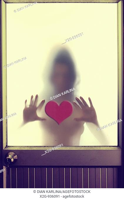 A woman behind frosted-glass door touching a heart shaped cut-out