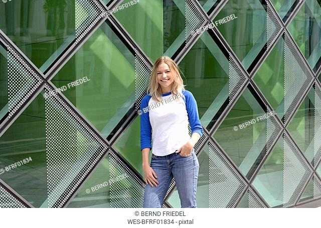 Blond young woman leaning on a glass facade