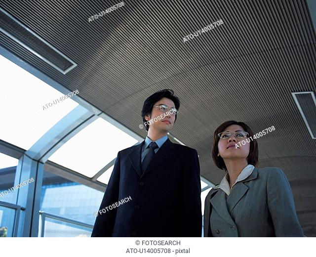 Businessman and businesswoman walking together, Low Angle View