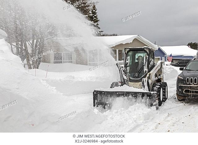 Grand Marais, Michigan - An industrial snow blower clears snow from a street in a town on Lake Superior in Michigan's upper peninsula