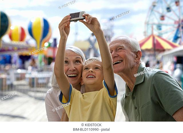 Caucasian couple with grandson at amusement park