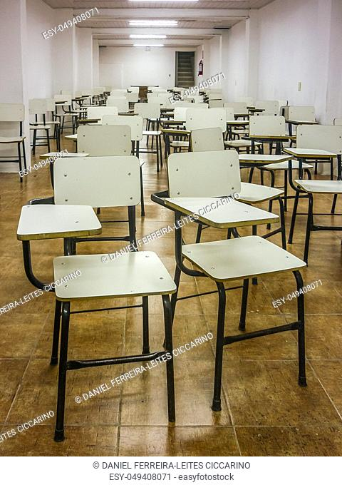 Perspective view of a big group of empty classroom white chairs