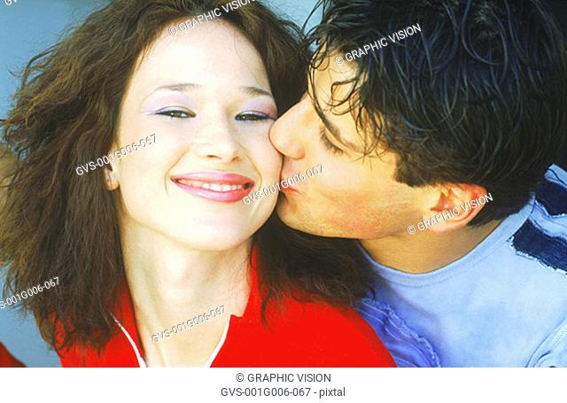 Portrait of young man kissing a young woman on the cheek