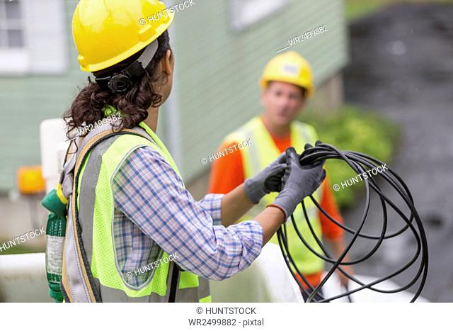 Hispanic female cable lineman looping the cable in bucket lift