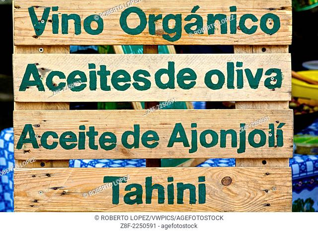 A wooden sign with the words: organic wine, olive oil, sesame oil and tahini in spanish