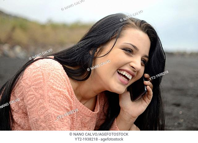 Cute brunette teenager on the beach, talking on the mobile telephone