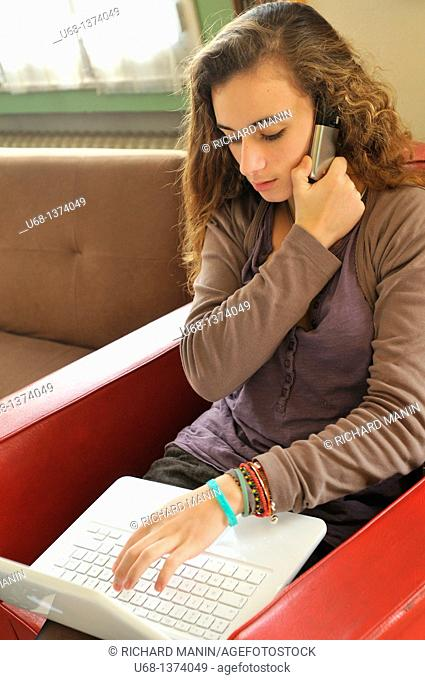 Teen girl using with cell phone and laptop computer