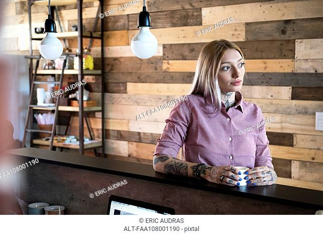 Young woman relaxing at counter in coffee shop
