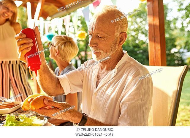Senior man preparing a hot dog on a garden party