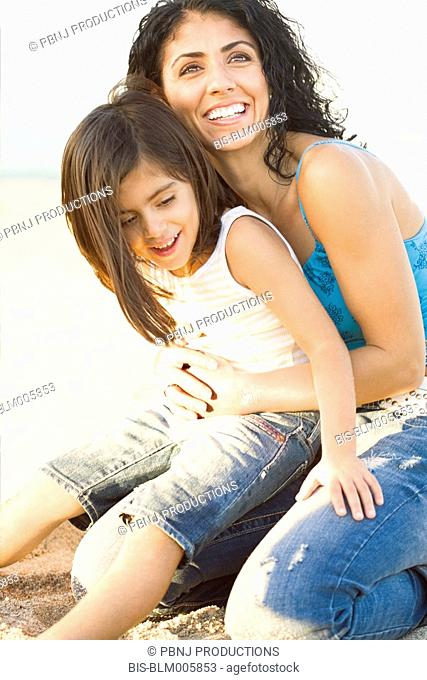 Mixed race mother holding daughter in lap