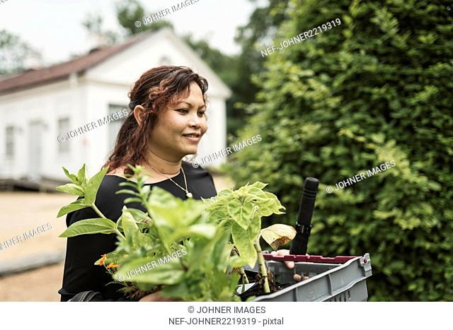 Woman carrying plants