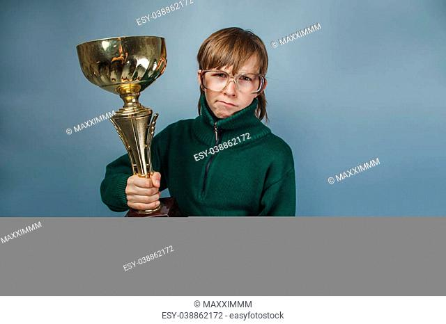 European-looking boy of ten years in glasses holding a cup in his hand, the reward on a gray background