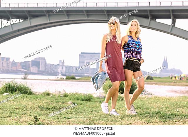 Two smiling young women walking at riverbank