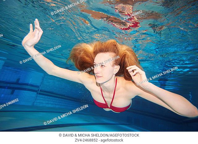 A young woman under water in swimsuit