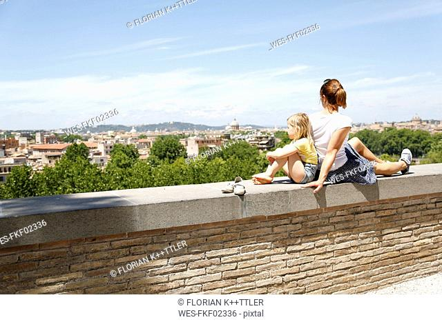 Italy, Rome, mother and her little daughter sitting back to back on a wall looking at view