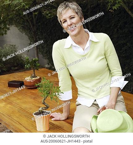 Portrait of a mature woman sitting on a table and smiling
