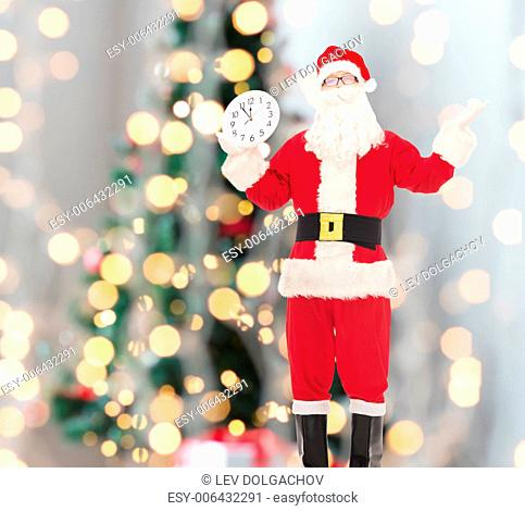 christmas, holidays and people concept - man in costume of santa claus with clock showing twelve over tree lights background