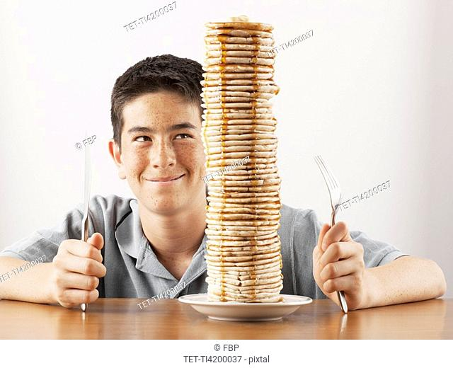 Young boy sitting behind a tall stack of pancakes