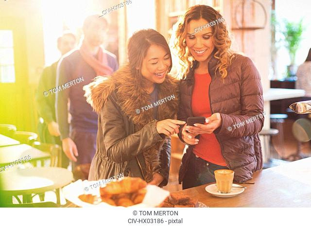 Women friends using cell phone in cafe